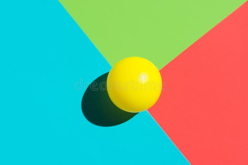 Yellow tennis ball on blue red green triangle elements. Abstract colorful graphic geometric composition. Business innovation. Technology modern arts stock photography