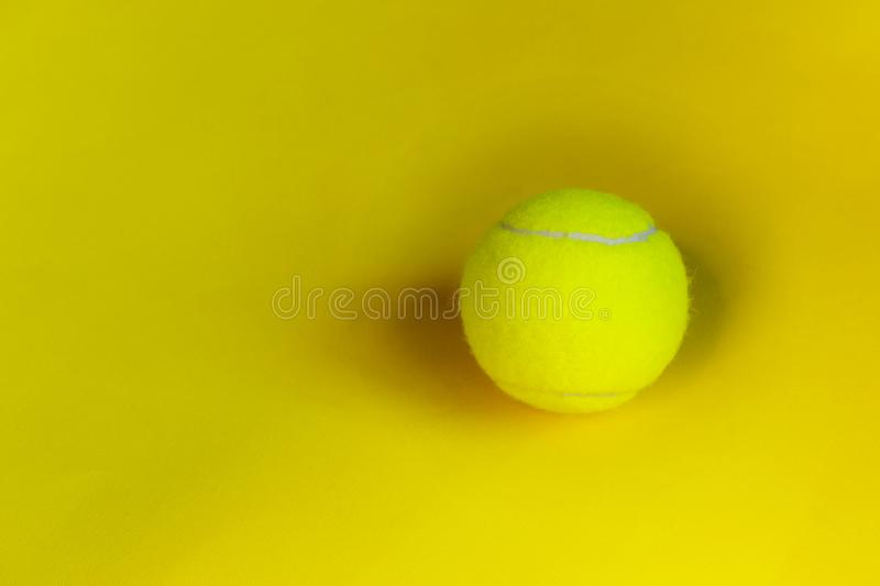 Yellow tennis ball over yellow background. Abstract sport background. royalty free stock image