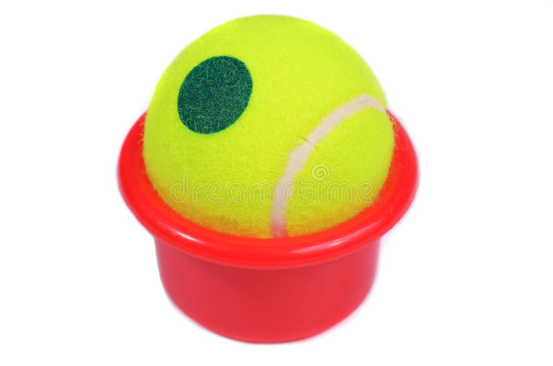 Yellow tennis ball in a red bucket. On white background stock photo