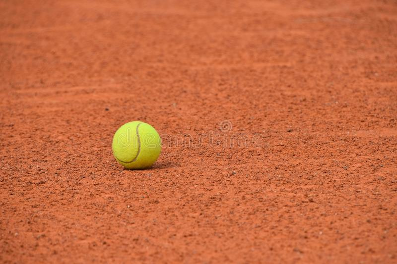 Yellow tennis ball on red clay ground court. Close up one yellow felt tennis ball on red brown clay ground court, low angle view royalty free stock photo