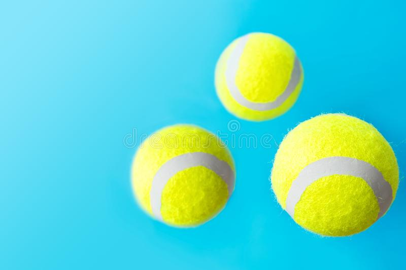 Yellow tennis balls floating levitating in air on light blue background active lifestyle competition victory concentration concept stock image