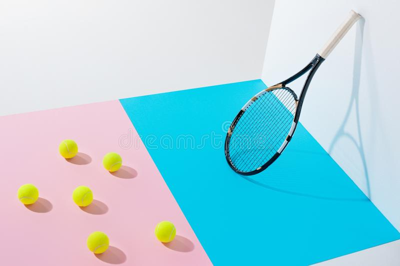 yellow tennis balls on pink paper and tennis racket on blue stock image