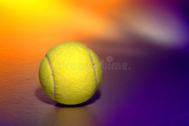 Yellow Tennis Sport Ball over Purple Background stock photography