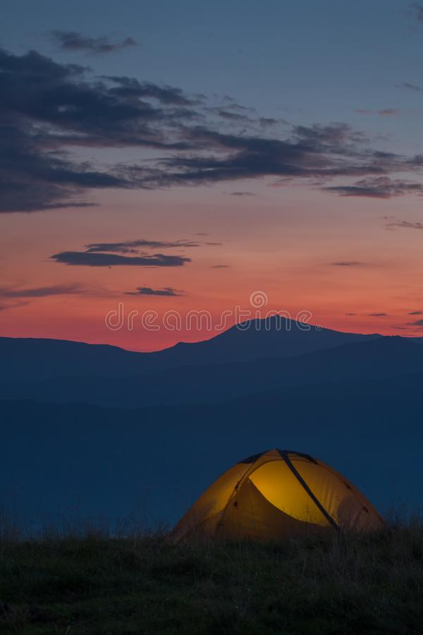 A yellow tent in mountains royalty free stock photos
