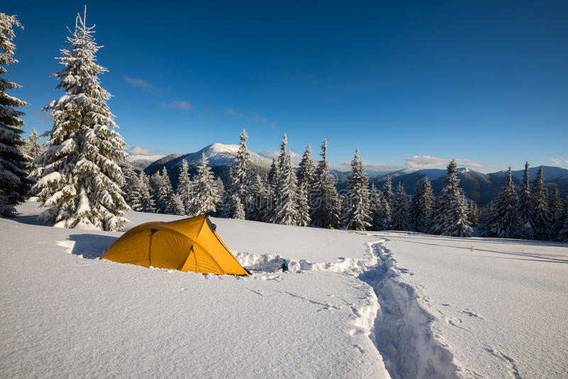 Yellow tent and snowshoes are standing at alpine meadow royalty free stock photo