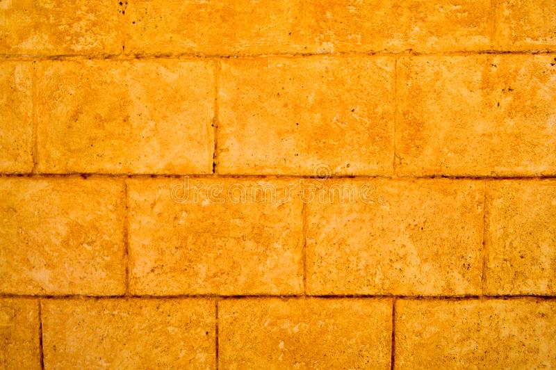 Yellow texture of the old ancient brick stone wall with tiles, blocks with seams. royalty free stock photography