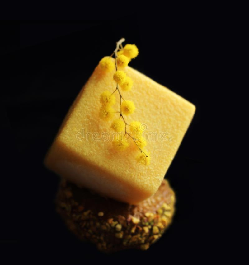 Yellow textured cube dessert with fresh mimosa flowers. Yellow textured cube dessert on pistachio base with fresh mimosa flowers isolated on black background stock image