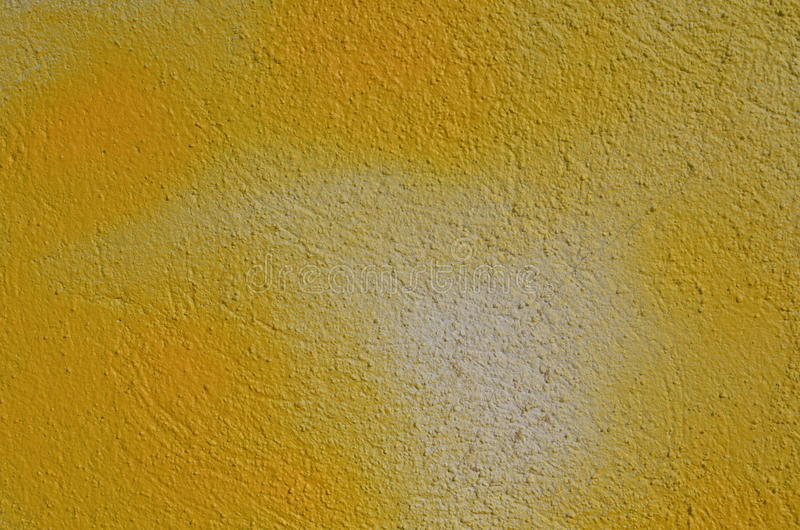 Yellow textured wall. Textured wall airbrushed by yellow graffiti paint stock image
