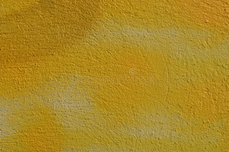 Yellow textured wall. Textured wall airbrushed by yellow graffiti paint royalty free stock photography
