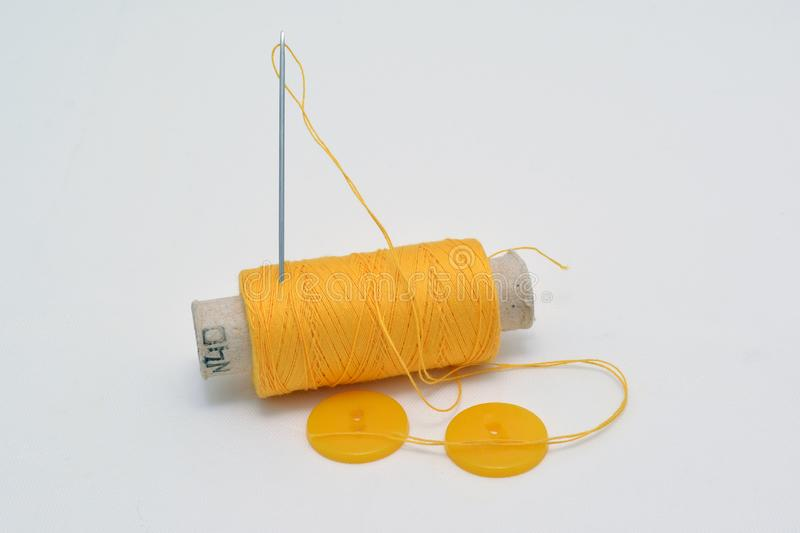 Yellow thread with needle and yellow buttons. royalty free stock photos