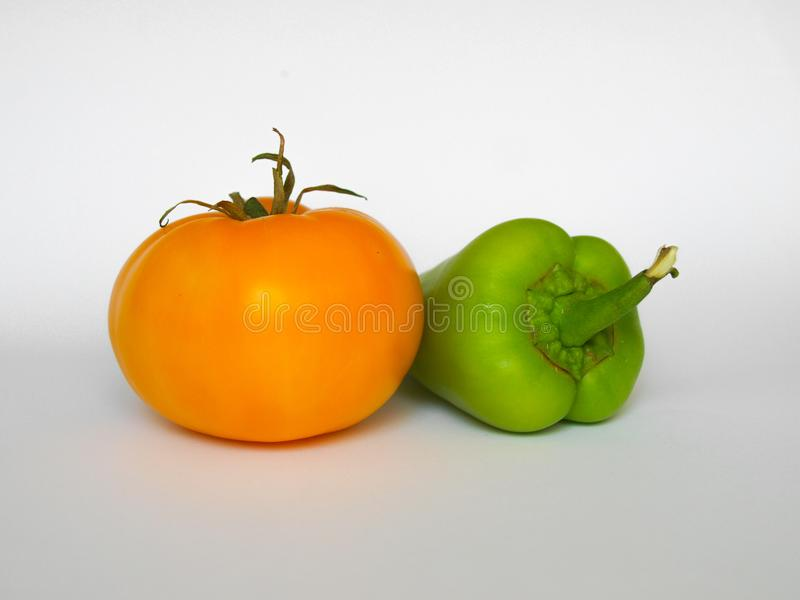 Yellow tomato and green pepper. stock image