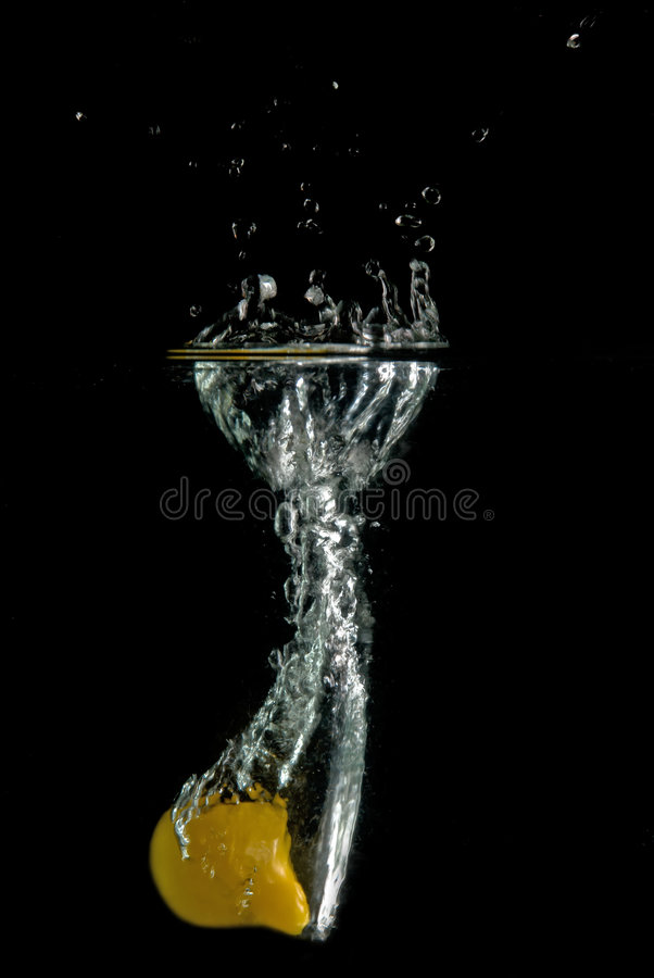 Yellow tomato splash. Yellow tomato thrown into the water royalty free stock photography