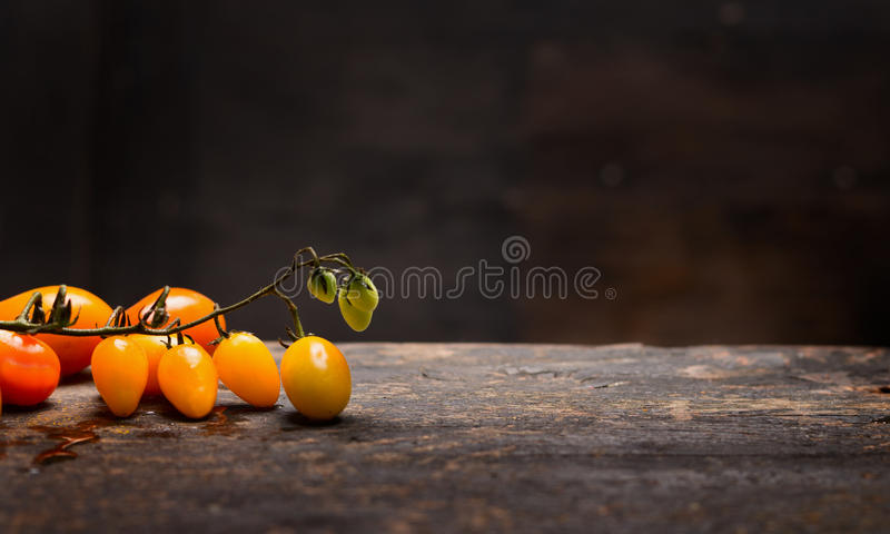 Yellow tomatoes branch on rustic table over dark wooden background, healthy food. Concept stock photography