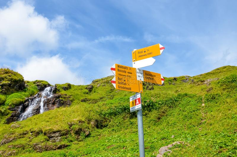 Yellow tourist sign in Bachlager, Switzerland giving distances and directions to hikers in the Swiss Alps. Popular hiking paths by. Grindelwald leading to royalty free stock images
