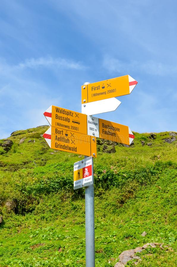 Yellow tourist sign in Bachlager, Switzerland giving distances and directions to hikers in the Swiss Alps. Popular hiking trail by. Grindelwald leading to royalty free stock image