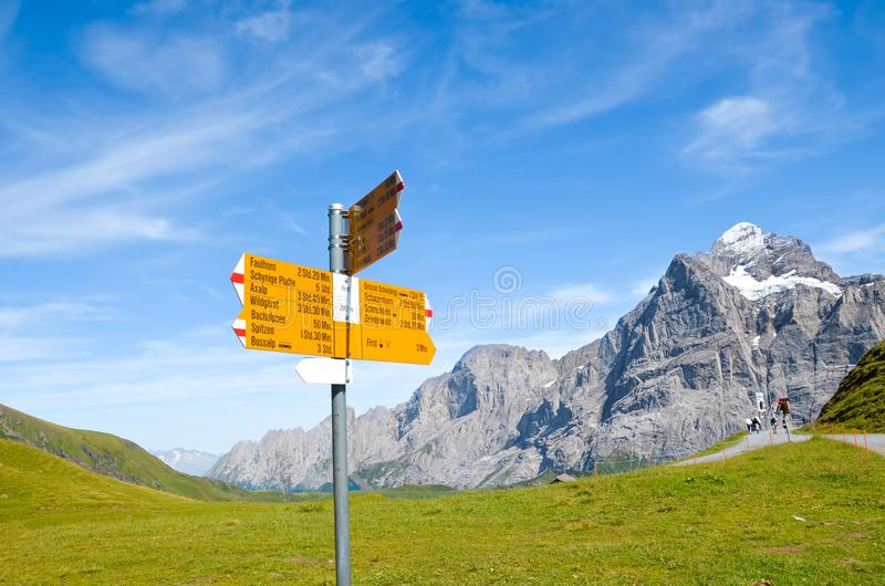 Yellow tourist sign in First, Switzerland giving distances and directions to hikers in the Swiss Alps. Popular hiking paths by. Grindelwald leading to stock photography