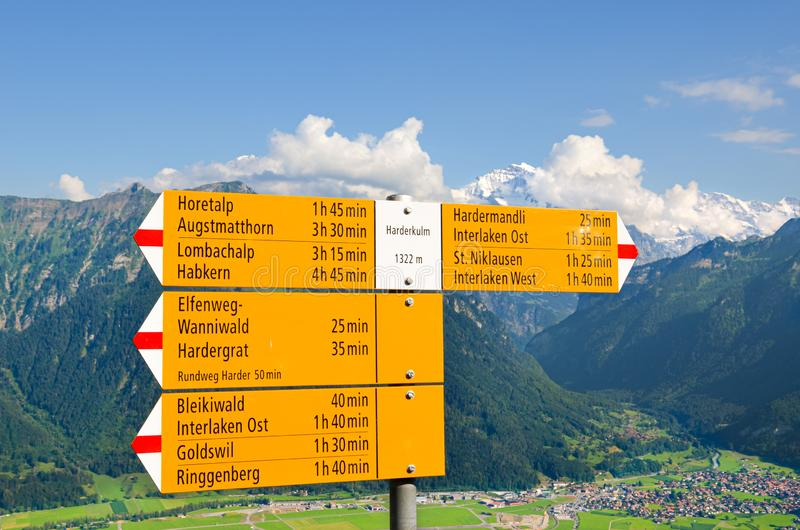 Yellow tourist sign on the top of Harder Kulm, Interlaken, Switzerland. The information sign specifies the directions and. Distances. Amazing summer Alpine stock photo