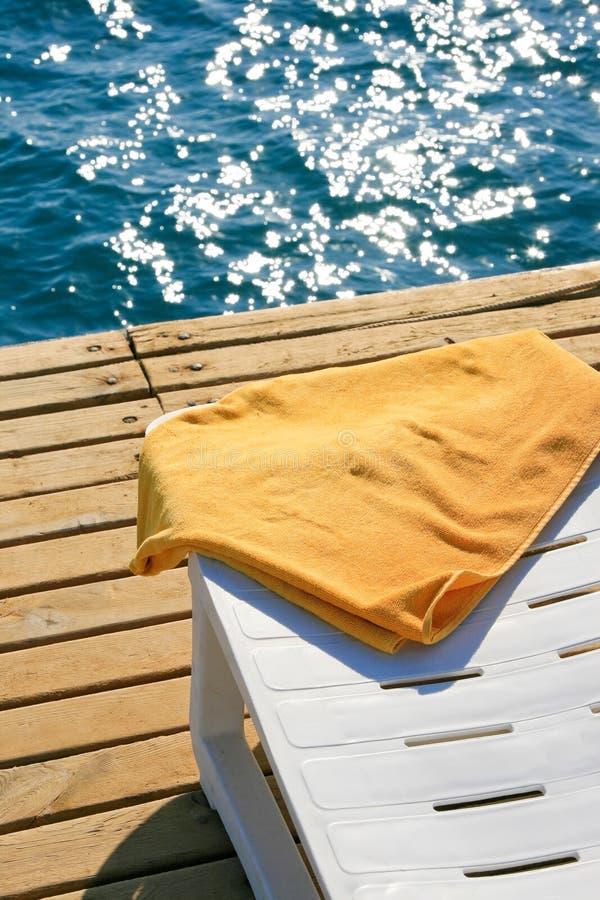 Yellow towel on lounge chair stock photo