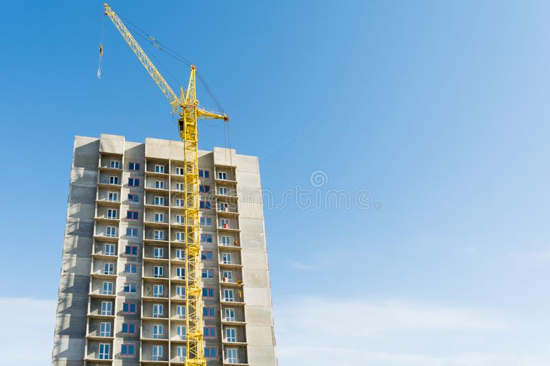 Yellow tower crane and the construction of a multi-storey building against a blue sky royalty free stock photos