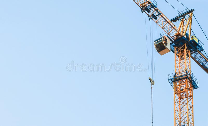 Yellow tower cranes at construction site. Construction site with cranes against blue sky. Construction crane working at stock photography