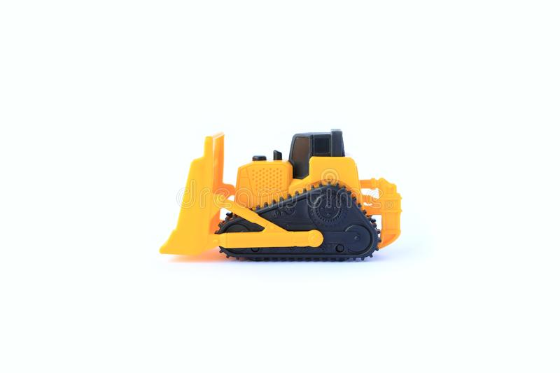 The yellow toy car Bulldozer isolated on white background. Children`s tractor toy. Wheel loader construction car model royalty free stock image