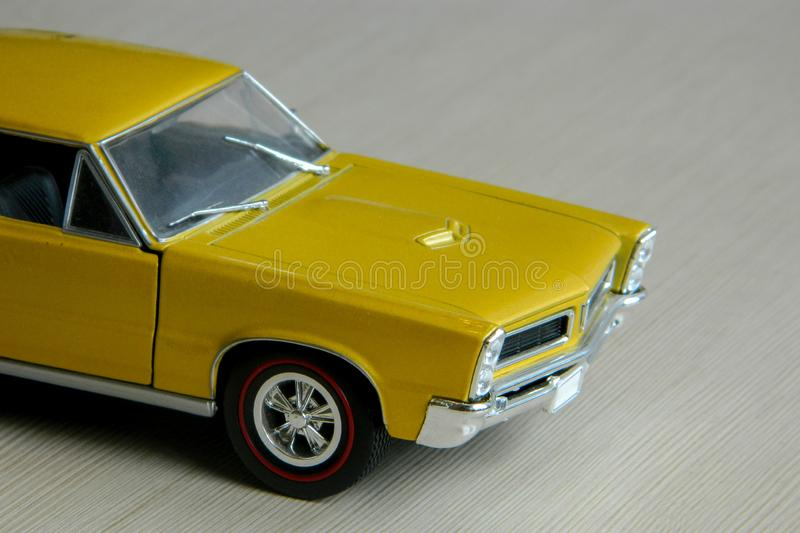Yellow toy car on gray striped surface. Model of classic muscle car with shadows and partly soft focus. Perspective view of auto royalty free stock photography