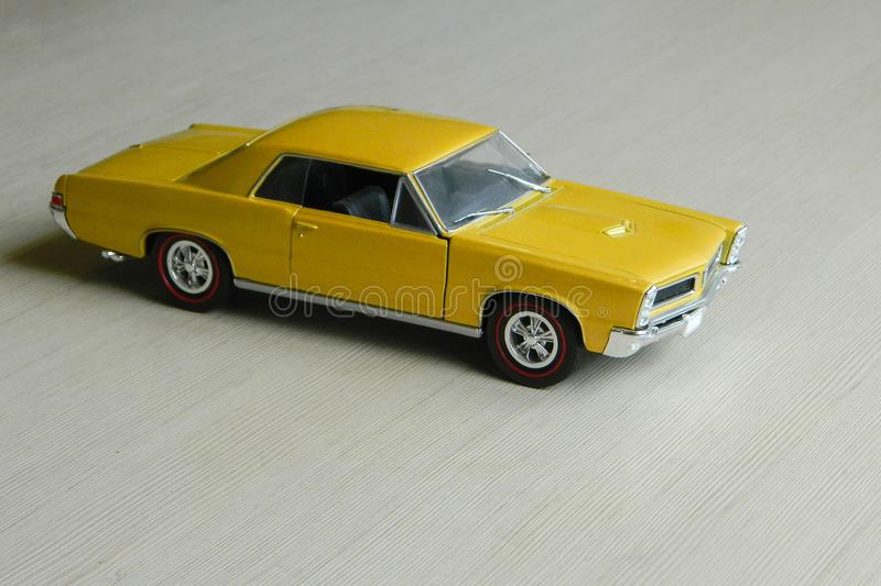 Yellow toy car on gray striped surface. Model of classic muscle car with shadows and partly soft focus. Perspective view of auto royalty free stock photo