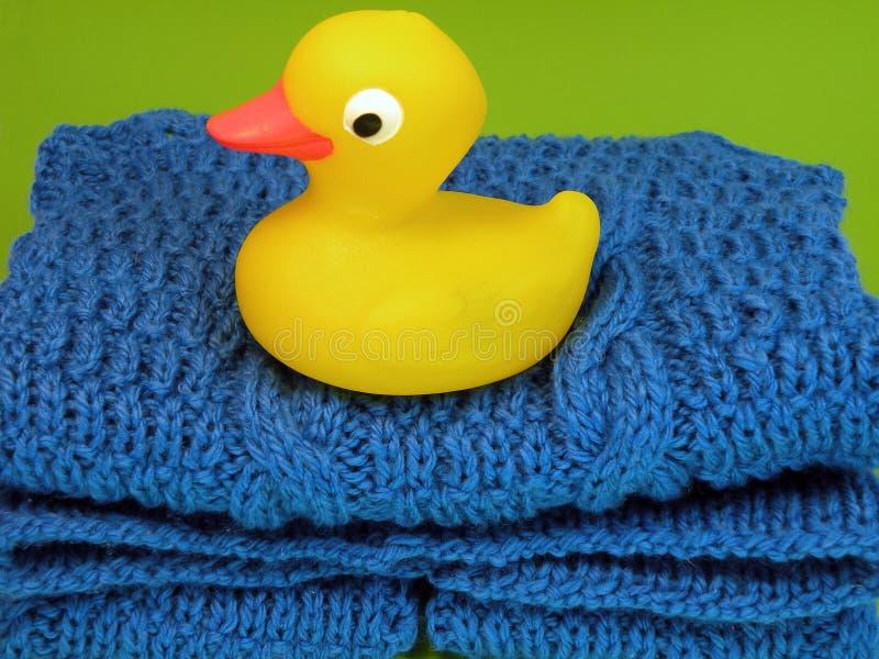 Yellow toy duck on children dress stock photos