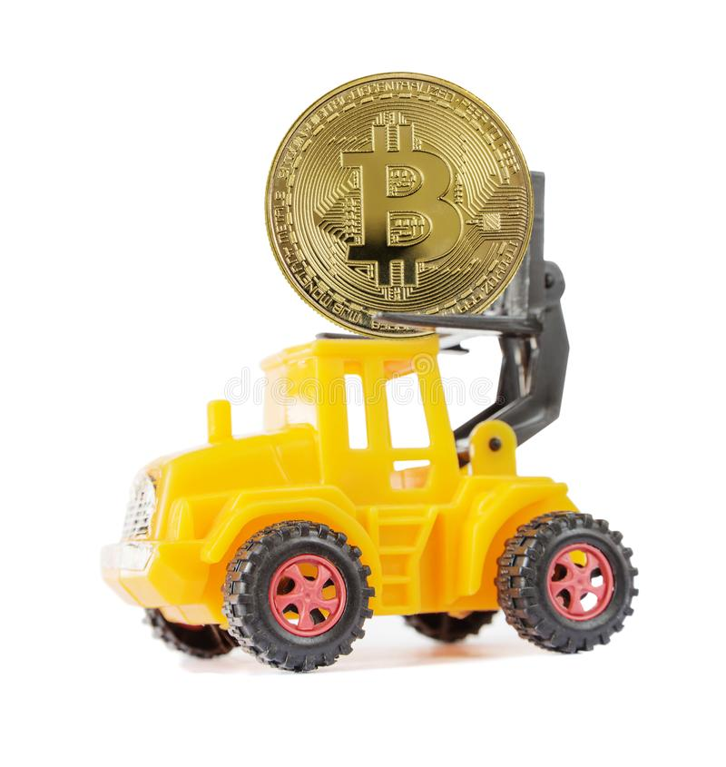 Yellow toy forklift carries bitcoin royalty free stock photography