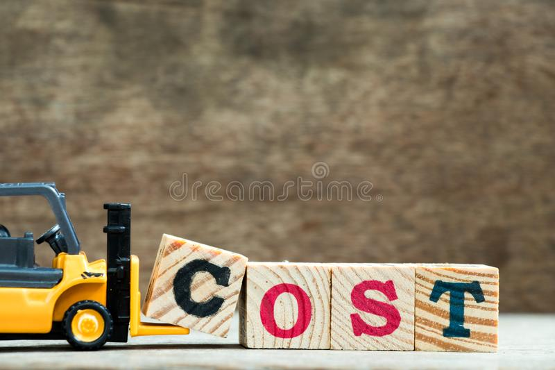 Yellow toy forklift hold letter block C to complete word cost on wood background stock photo