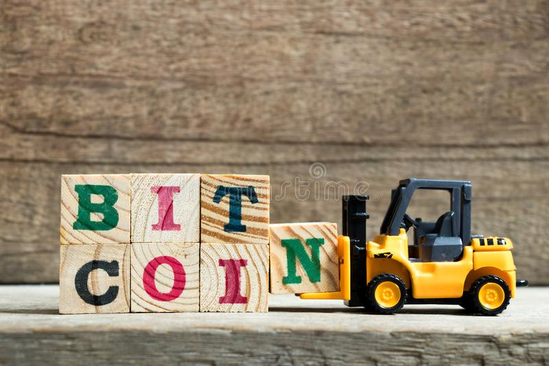 Yellow toy forklift hold letter block N to complete word bitcoin on wood background stock images