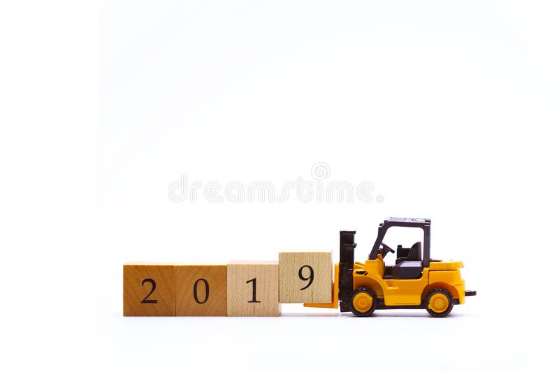 Yellow toy forklift lifting wooden block number 9 to complete word 2019. Isolated on white background with copy space. For business, investment, logistic, and royalty free stock photography