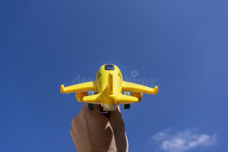 Yellow toy plane flying in to the beautiful blue sky, negative space, concept of going on a magical holiday. Dream destination stock photography