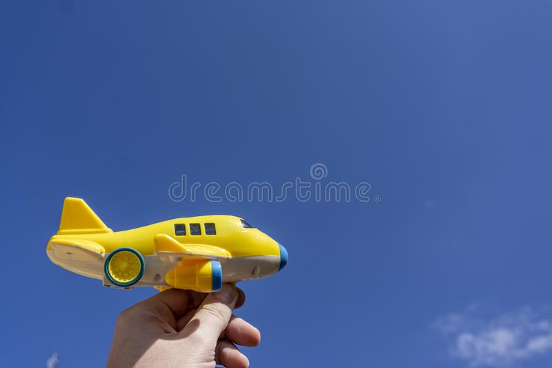 Yellow toy plane flying in to the beautiful blue sky, negative space, concept of going on a magical holiday. Dream destination stock photos