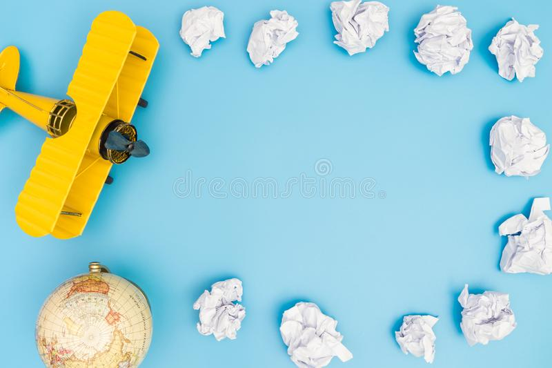 Yellow toy plane on paper cloud on blue copy space royalty free stock photography