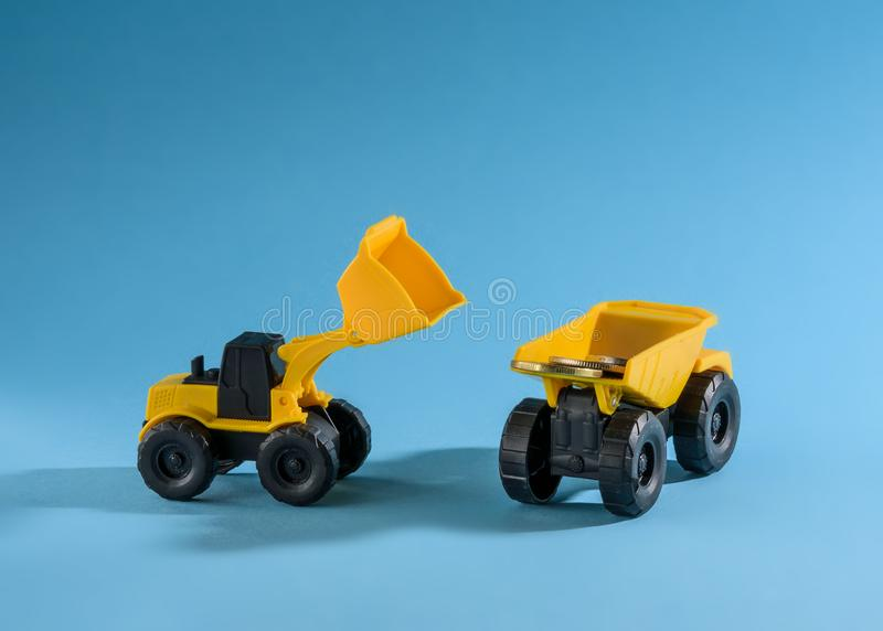 Yellow toy truck and bulldozer loading coins. space for text. royalty free stock photos