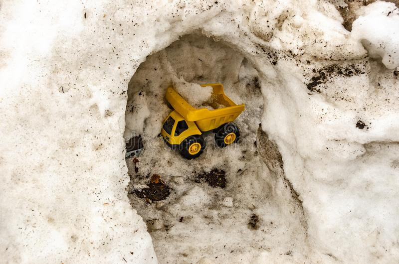 Yellow Toy Truck Hauling Snow. Toy dump truck carrying snow through a hollowed out snow bank royalty free stock photography