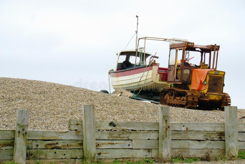 Crawler and boat on shingle beach. Yellow tracked vehicle towing a crabbing boat on a trailer on the shingle beach at Weybourne Norfolk UK royalty free stock photos