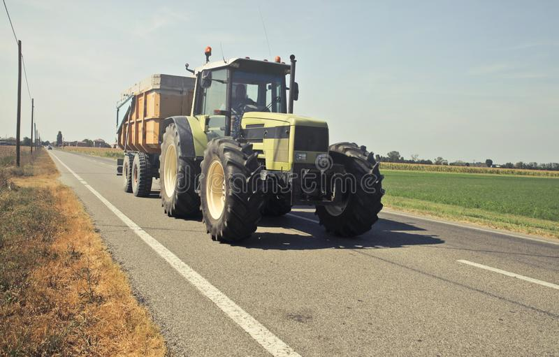 Yellow Tractor in Asphalt Road stock photography
