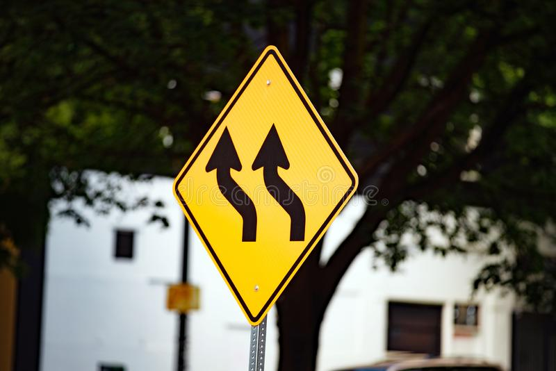Yellow traffic sign with wavy black arrows royalty free stock image