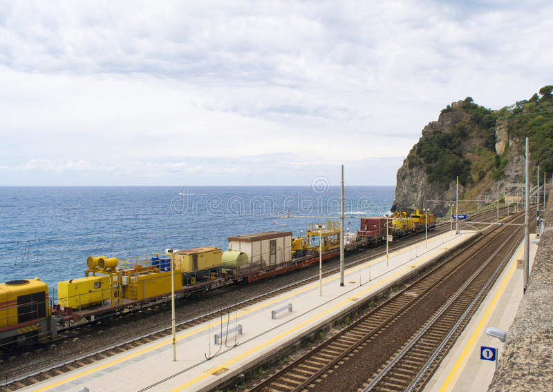 Yellow train in front of the ocean in Corniglia, Italy. Yellow construction train parked in front of the Mediterranean sea in Corniglia, Cinque Terre, Liguria stock images