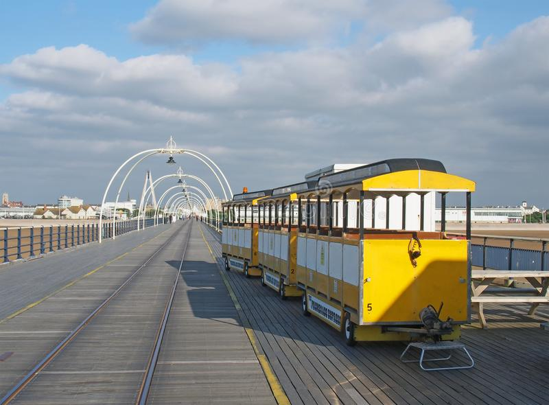 The yellow train on the pier in southport merseyside on a bright summer day with town buildings against a blue cloudy sky. Southport, merseyside, united kingdom royalty free stock photo
