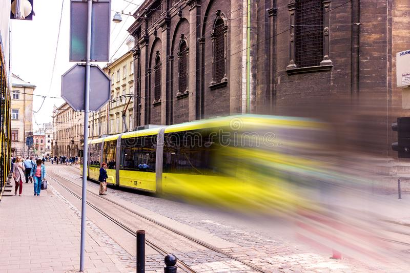 Yellow tram with motion blur effect moves fast in the city. High speed passenger train in motion on railroad. Modern urban rail stock photo