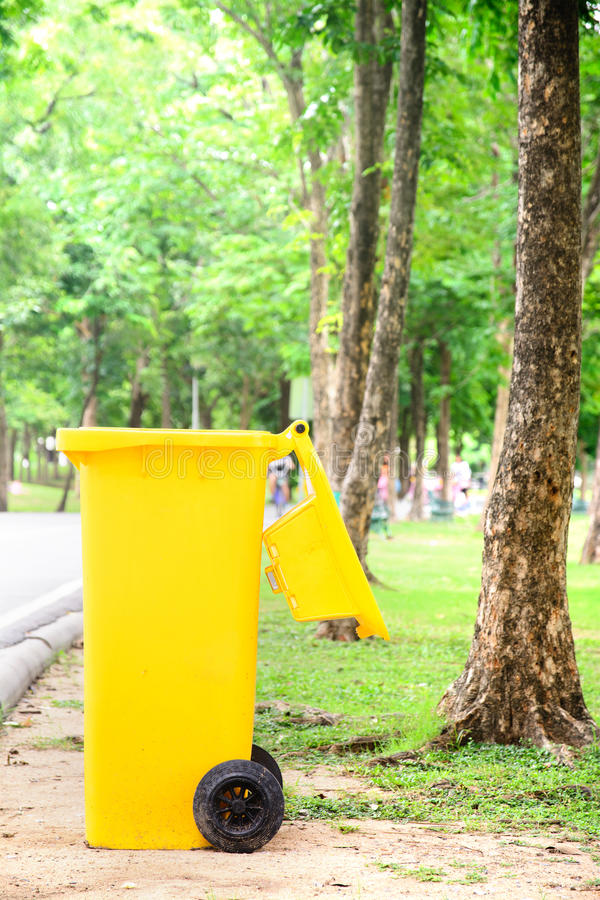 Yellow trash bin. In park royalty free stock photography
