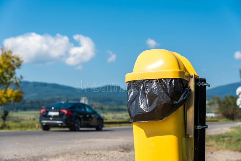 Yellow trash can near road, passing car. Blue sky background stock images