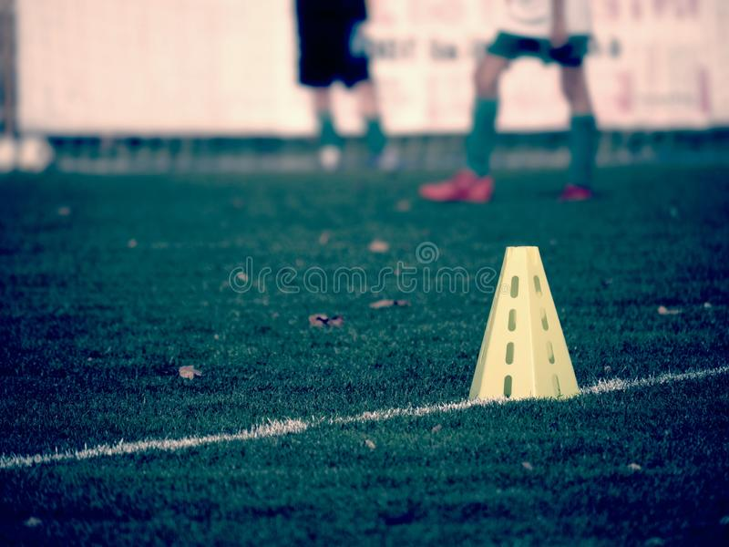 Yellow triangles used as soccer training equipment. On green grass field royalty free stock image