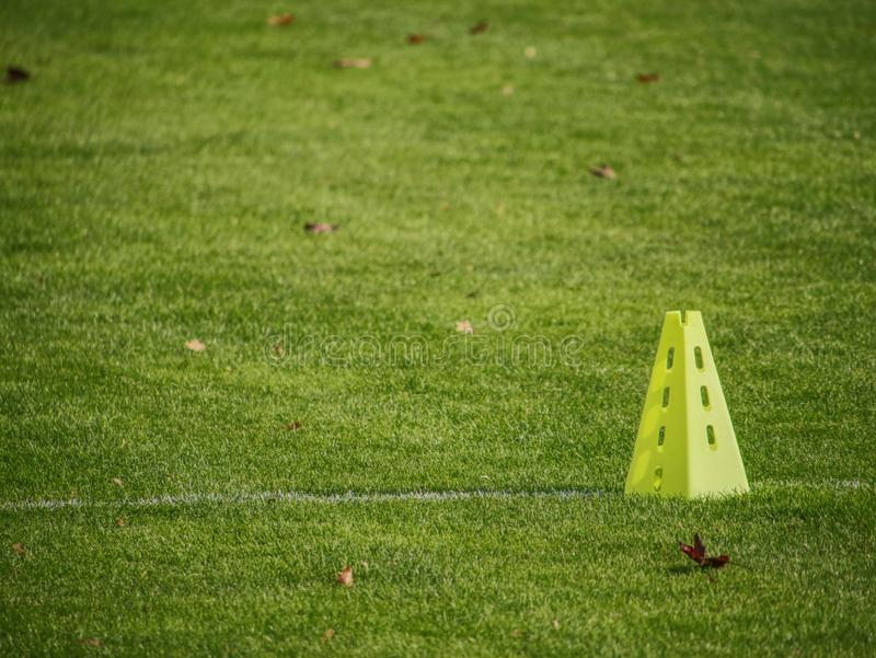 Yellow triangles used as soccer training equipment. On green grass field royalty free stock photo
