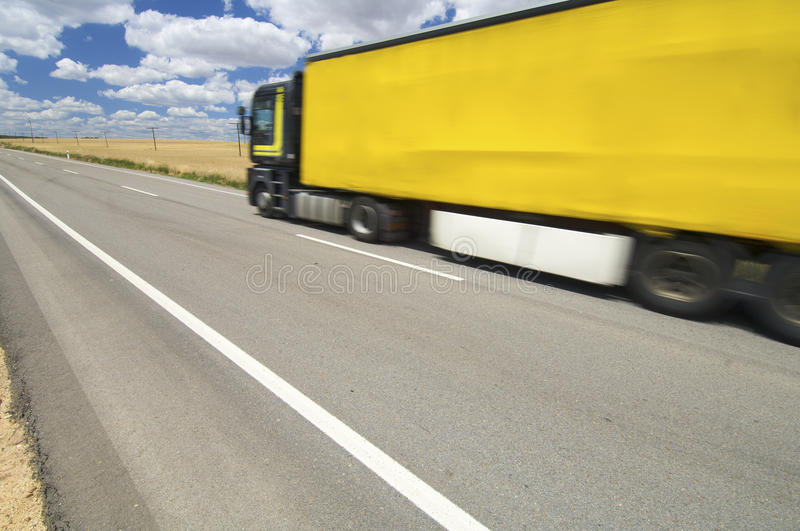 Yellow truck. Circulating yellow truck speeding along a straight road royalty free stock photography