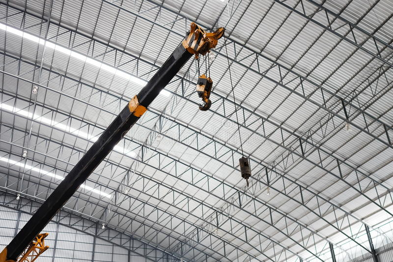 Yellow truck crane boom with hooks in the warehouse. Indoor lighting. The background is the new roof of warehouse stock images