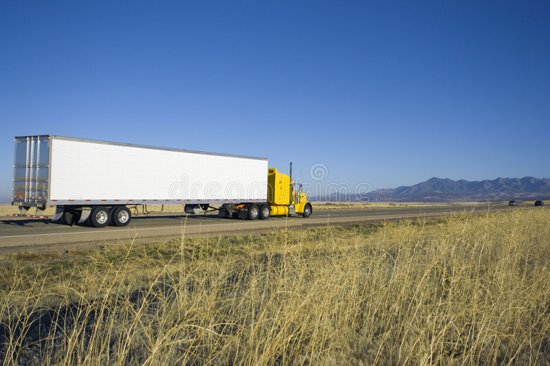 Yellow truck driving towards mountains. royalty free stock images